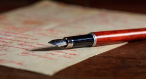 Handwritten letter and an ink pen on a wooden desk