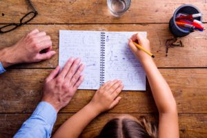 Unrecognizable father and son together, writing into notebook